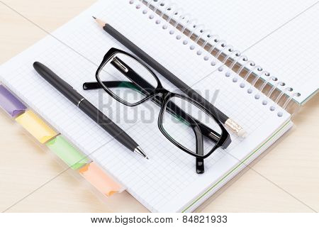Office table with glasses over notepad, pen and pencil. Top view