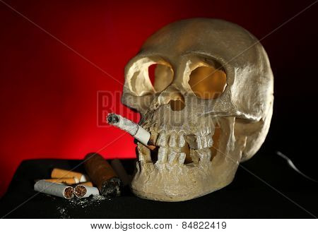 Smoking human scull with cigarette in his mouth on dark color background