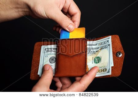 Man holding hand made leather wallet with cards and money on black background