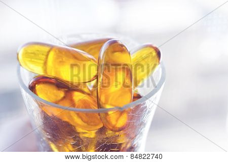 Glass full of  Cod liver oil capsules