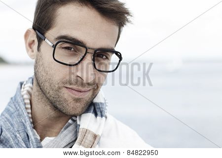 Portrait of mid adult man and spectacles on beach