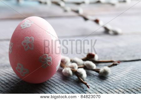 Bird colorful egg in nest and pussy willow branches on wooden background
