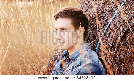 handsome man sitting in a cornfield