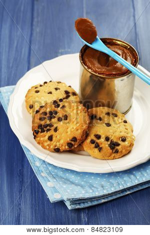 Can of boiled condensed milk with spoon and cookies in plate on color wooden table background