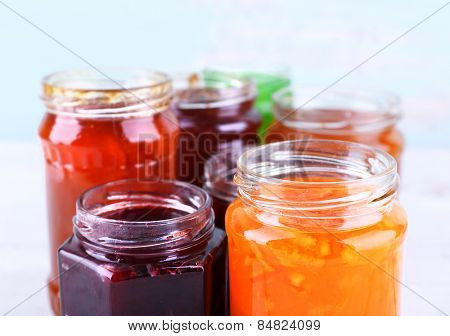 Homemade jars of fruits jam on table and color wall background