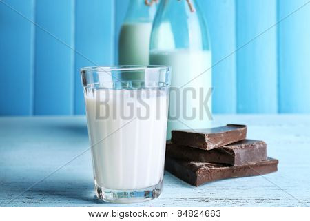 Glass and bottles of milk with chocolate chunks on color wooden planks background