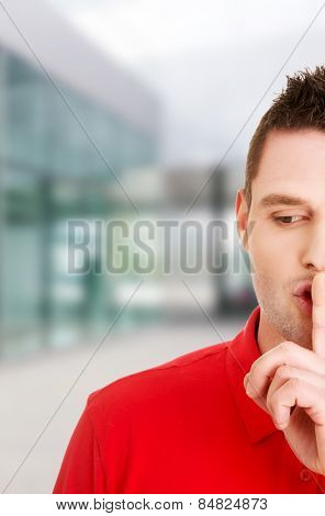 Man gesturing to be quiet with finger