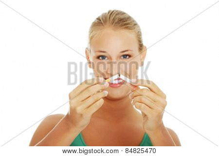 Young blonde woman breaking cigarette