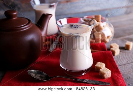 Black tea with milk in glasses and teapot with lump sugar on color wooden planks background