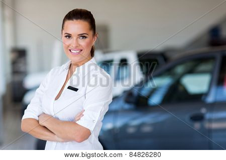 pretty female car dealer with arms crossed