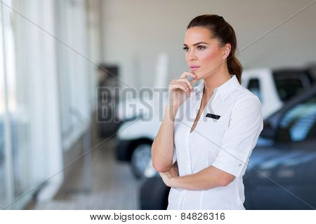 thoughtful female car dealership principal standing in showroom