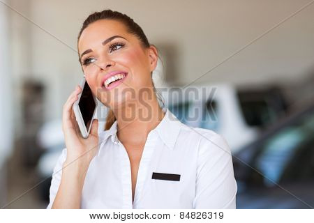 cheerful car saleswoman talking on cell phone