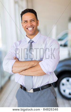 good looking vehicle salesman with arms crossed in car showroom