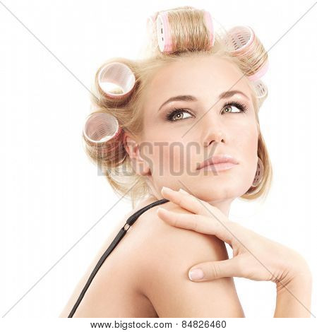 Portrait of attractive female with curlers on hair isolated on white background, making stylish hairdo, fashion and beauty concept