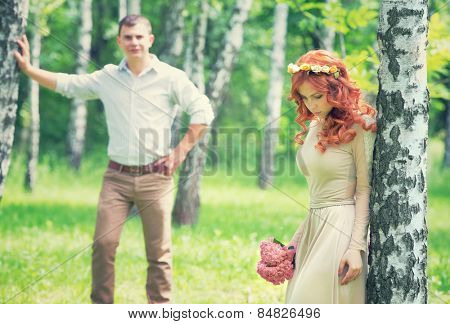 Loving couple walking between birch in the park on sunny day, back side, happy wedding day, love and romance