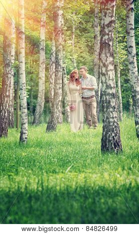 Loving couple walking between birch in the park on sunny day,  holding hands, happy wedding day, love and romance