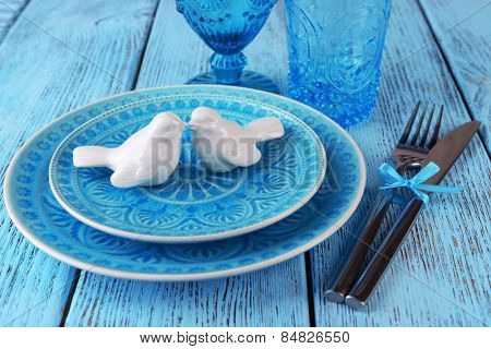 Empty colorful plate, glasses and silverware set on wooden table