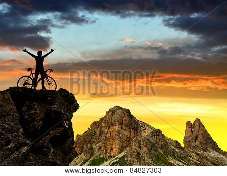 Silhouette of the cyclist on bike at sunset .In the background Dolomite Alps , Italy