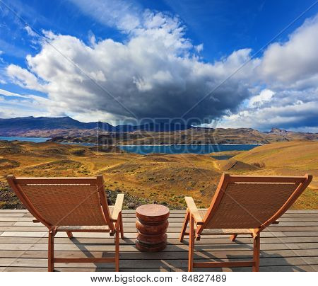 Pleasant holiday. Chile. Wooden chairs in the park Torres del Paine. On the horizon is visible snow-covered  mountain