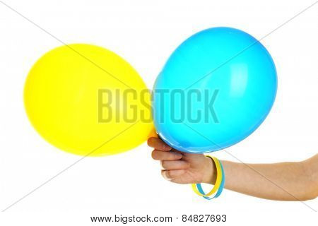 Hand holding blue and yellow balloons, isolated on white