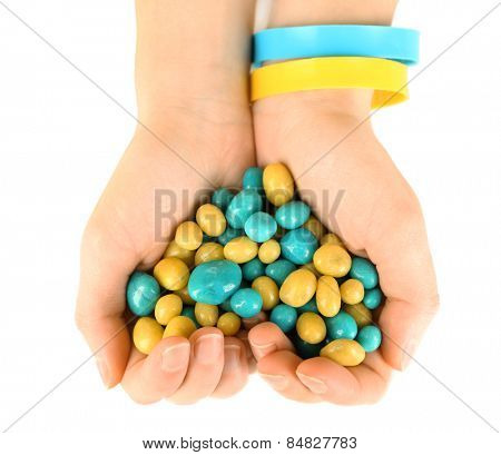 Hands with blue-yellow candies - colors of flag of Ukraine, isolated on white