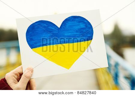 Hand holding paper heart with painted Ukraine flag