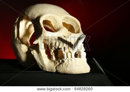 Smoking human scull with cigarette in his mouth on dark background