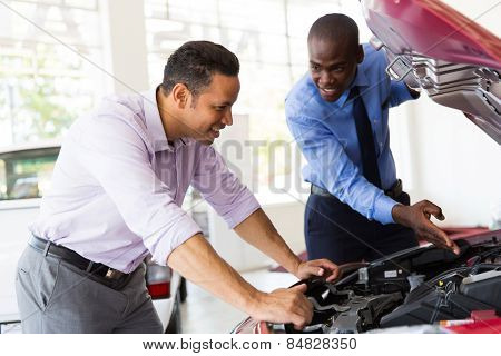 salesman and customer looking at a car engine in showroom