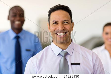 portrait of middle aged car dealership principal with staff on background