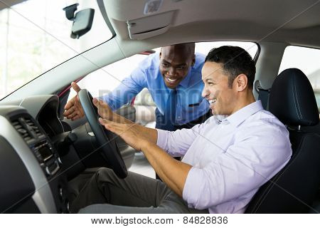 friendly african salesman explaining car features to customer