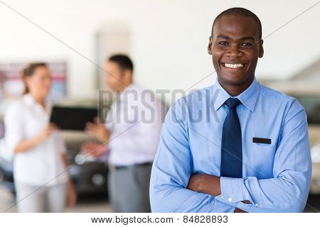 handsome african car salesman looking at the camera