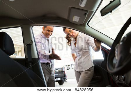 friendly car dealer showing new car to customer