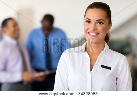 beautiful caucasian saleswoman standing at car dealership