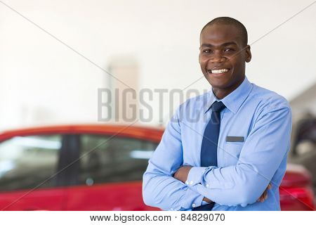 portrait of african american car sales consultant with arms folded in showroom