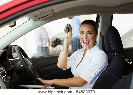 cheerful young woman showing her new car key at dealership