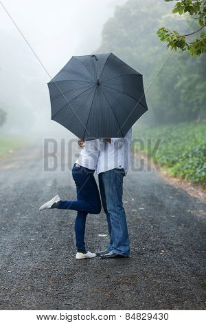 romantic young couple hiding behind the umbrella in the rain