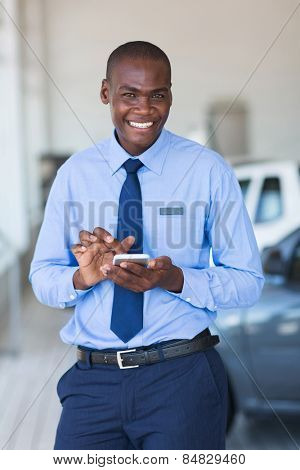 cheerful young african car salesman using smart phone