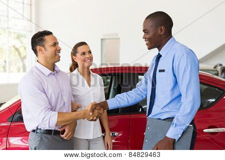 happy car salesman handshaking with middle aged buyer