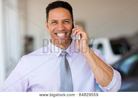 mid age man talking on smart phone at car dealership