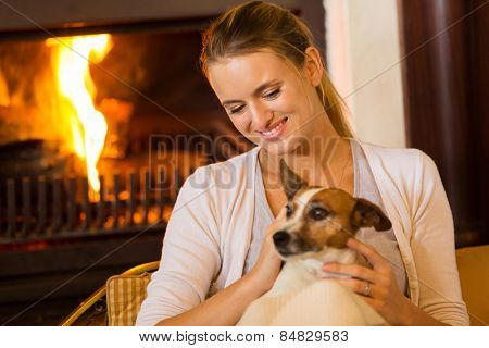 beautiful young girl sitting at home with her dog near fireplace