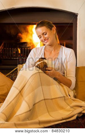 pretty young woman petting her dog at home near fireplace