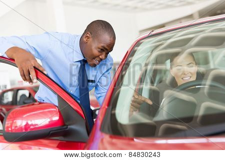 handsome african salesman explaining car features to potential customer
