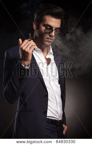 Handsome elegant business man looking down while holding a cigarette in his right hand.