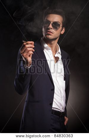 Elegant business man looking up while enjoying a cigarette.