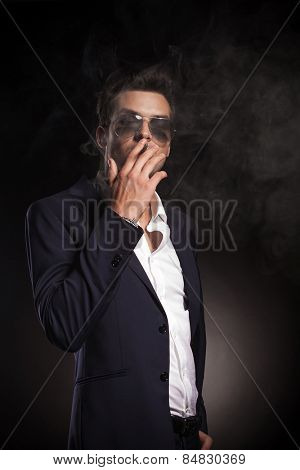 Portrait of a attractive young business man smoking o cigarette on black background.