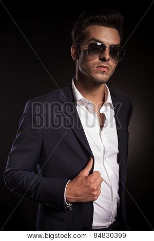 Elegant young business man looking away from the camera while arranging his jacket, on black studio background.