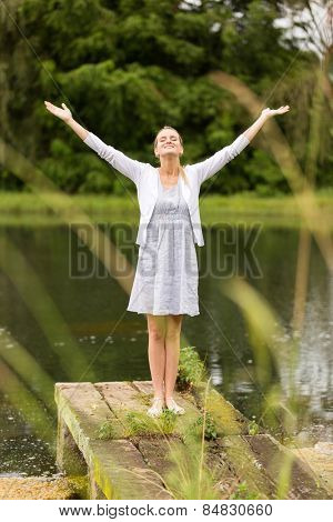 happy woman standing by lake with arms outstretched
