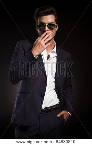Elegant business man smoking a cigarette while holding his hand in pocket.
