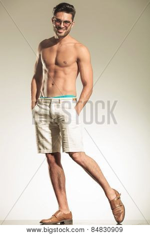 Sexy young casual man standing on studio background while holding his hands in pockets.