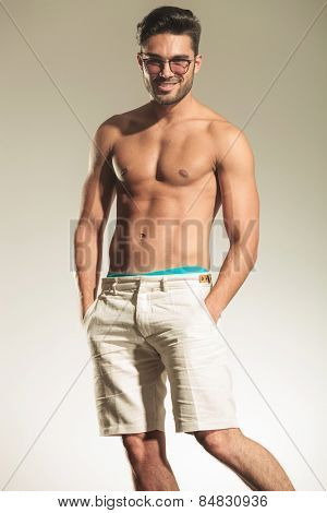 Portrait of a shirtless sexy man posing with his hands in pockets while smiling at the camera.